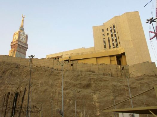 Abraj Al Bait Tower tampak serasi dan dekat dengan hotel di atas bebatuan ini, padahal aslinya keduanya tidak berdekatan. Saking tingginya tower Al Bait hingga bisa dilihat dari seluruh kota Mekkah dan sekitarnya. Sinar matahari pagi memberi efek warna keemasan pada bangunan.